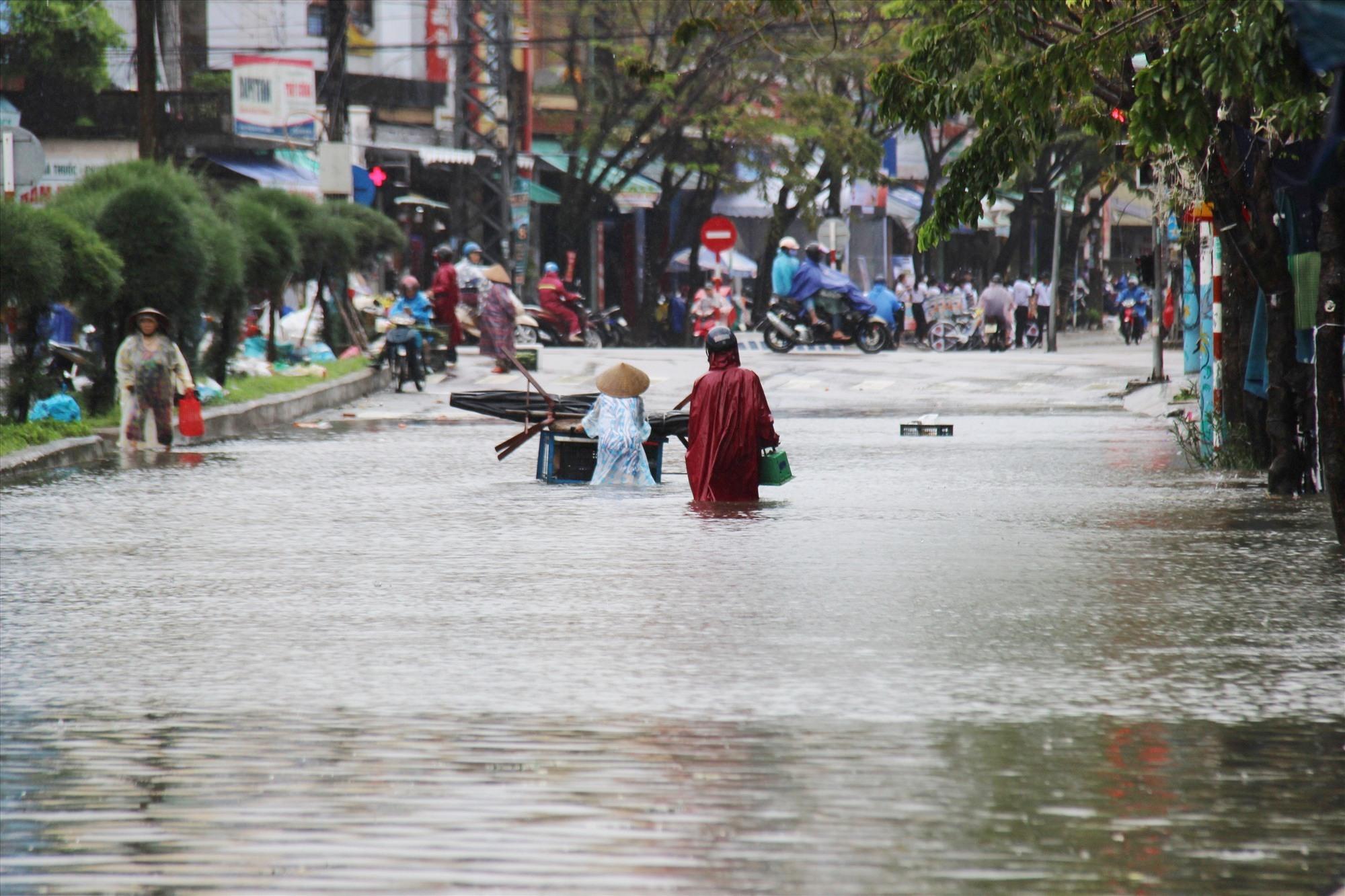 Người dân vượt qua dòng nước lũ. Ảnh: HOÀI AN