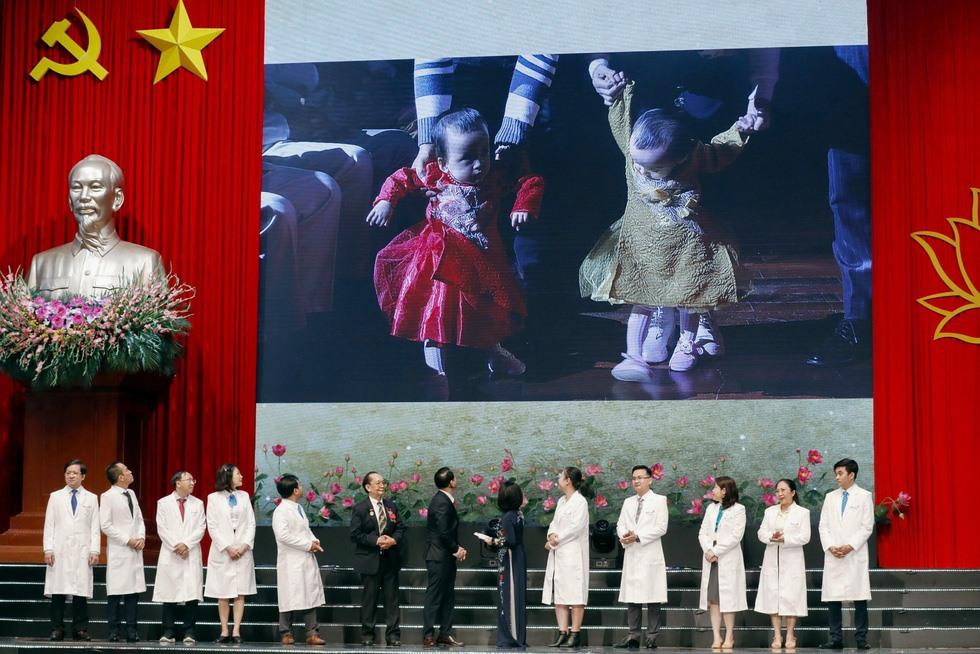 Hai bé Trúc Nhi và Diệu Nhi lẫm chẫm bước trên những bậc thềm tại hội trường trong cái nắm tay của cha mẹ sau ca mổ tách của các giáo sư, bác sĩ, y tá Bệnh viện Nhi đồng TP.HCM - Ảnh: VIỆT DŨNG