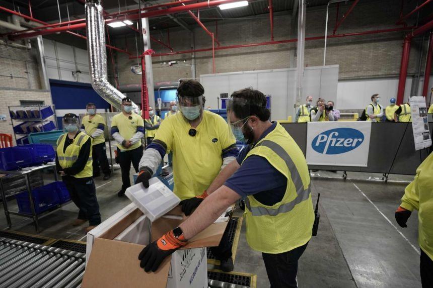 Các nhân viên chất hàng vắc xin Covid-19 của Pfizer tại nhà máy sản xuất ở bang Michigan. Ảnh: AFP