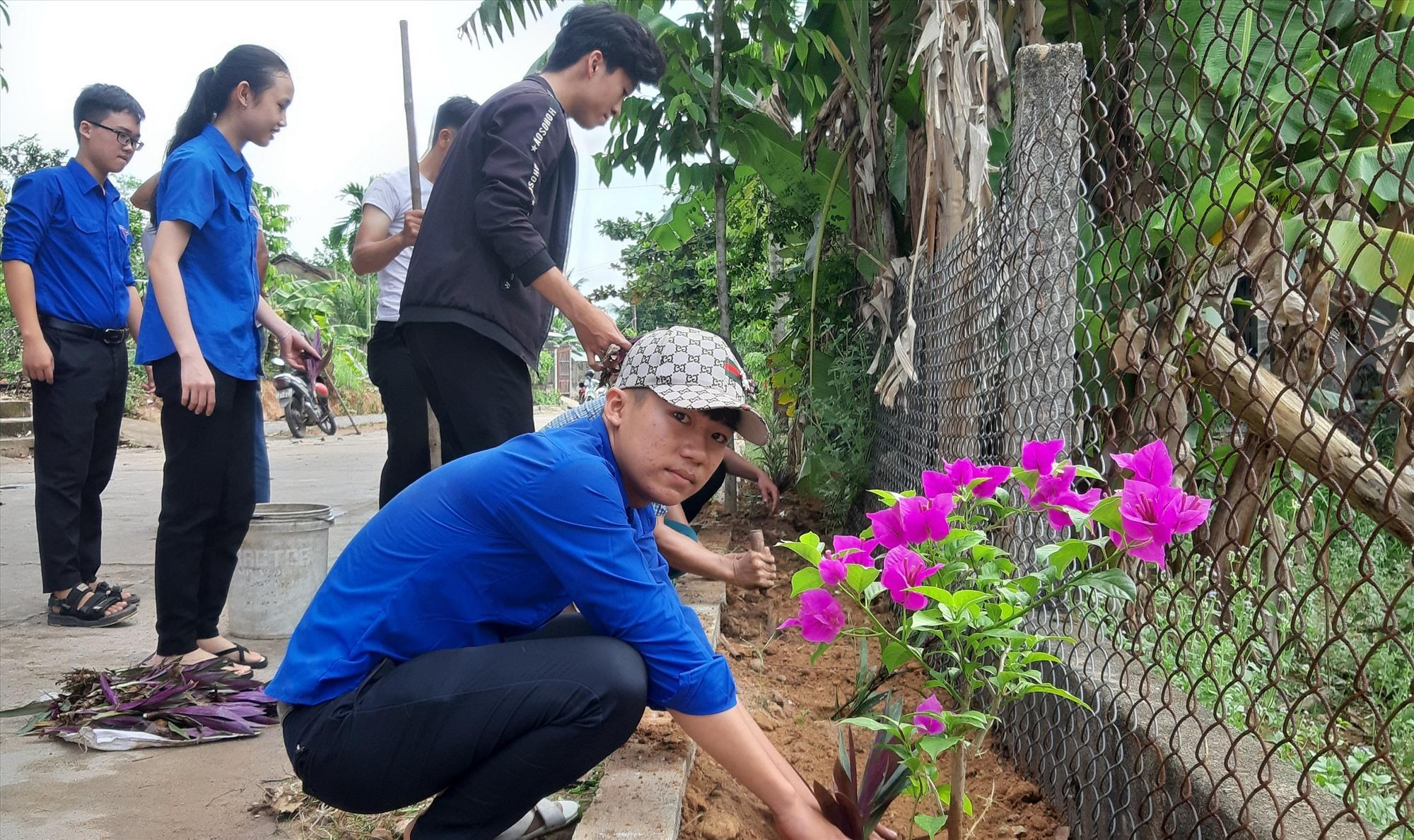 Người dân thôn Phú Bông (Duy Trinh, Duy Xuyên) ra quân trồng hoa thay thế cỏ dại trên các tuyến đường. Ảnh: HOÀI NHI