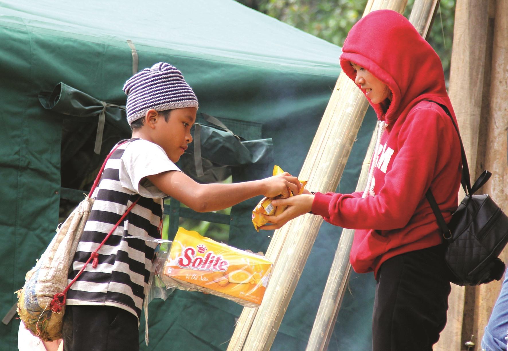 Cầm trên tay gói bánh vừa được đoàn thiện nguyện trao, cậu học trò người M'nông ở xã Trà Leng này lập tức chia sẻ với người đi đường. Hành động ấy khiến nhiều người cảm động.