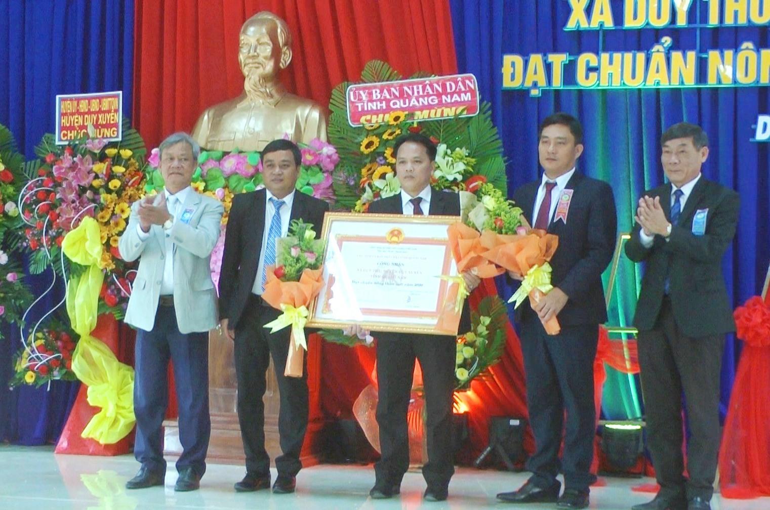 Đại diện lãnh đạo Văn phòng điều phối NTM tỉnh và huyện Duy Xuyên trao bằng công nhận xã đạt chuẩn nông thôn mới cho xã Duy Thu. Ảnh: T.P