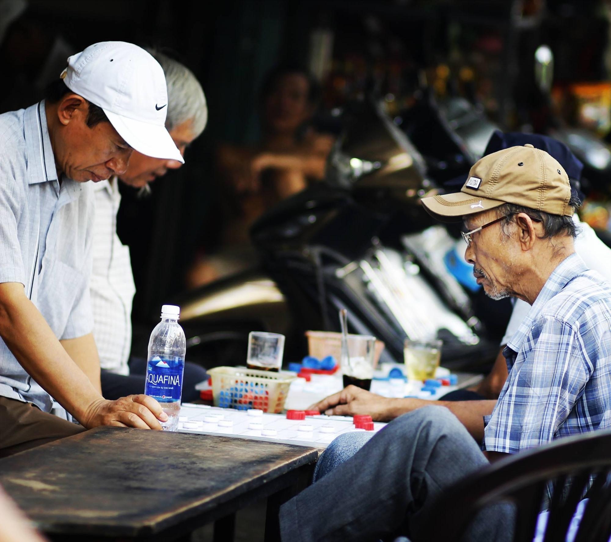 Những người đàn ông chơi cờ giữa phố khuya. Ảnh: T.V