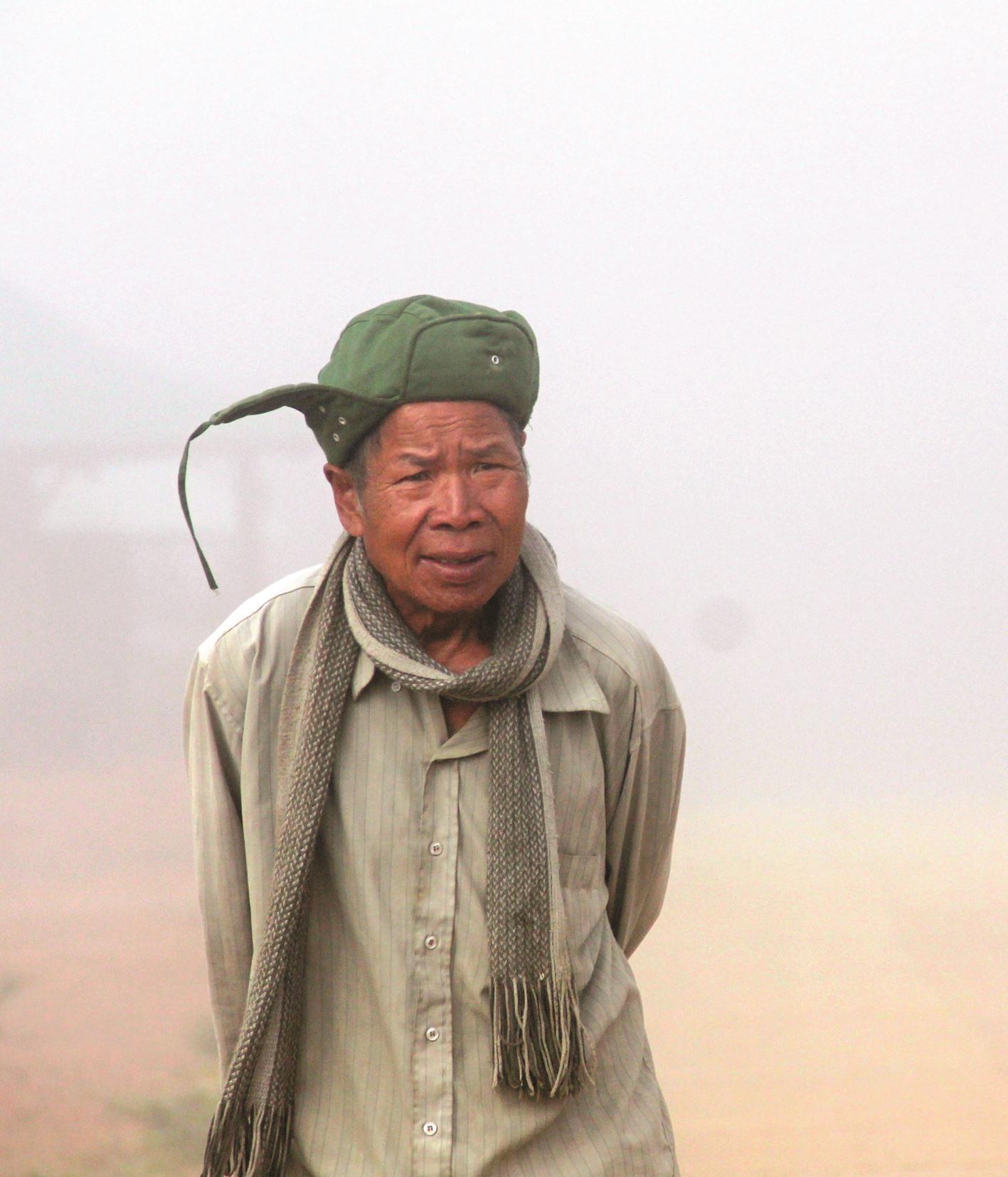 Một cụ già co ro trong màn sương sớm vùng cao.