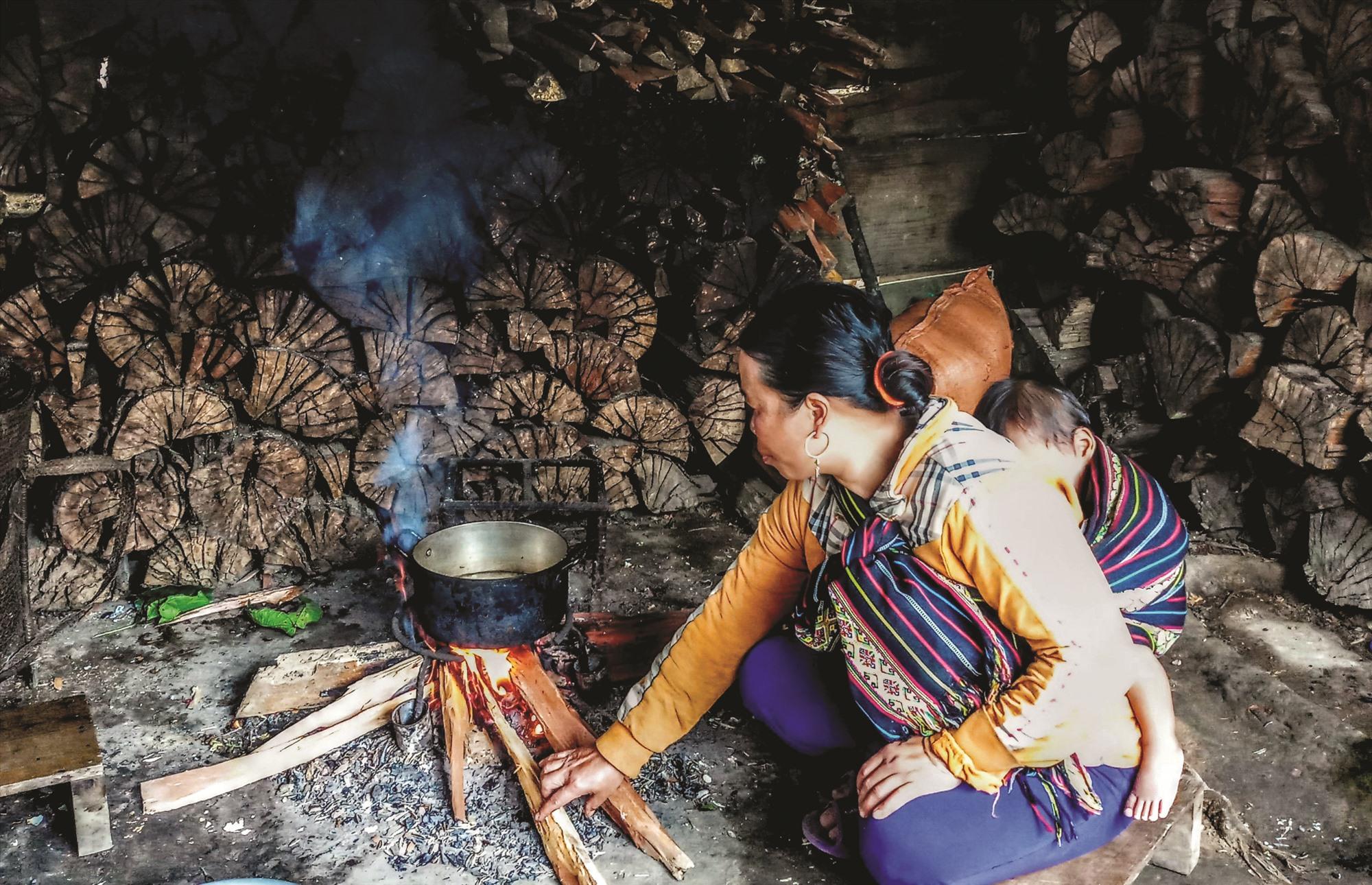 Một phụ nữ Cơ Tu tranh thủ vừa nấu cơm, vừa địu cháu để sưởi ấm.