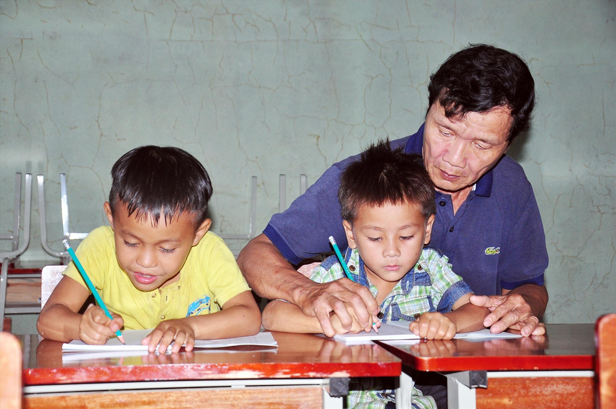 Thầy Lê Văn Bốn miệt mài chỉ bảo cho học trò ở điểm trường Tăk Rối sau cơn lũ đi qua. Ảnh: VINH ANH