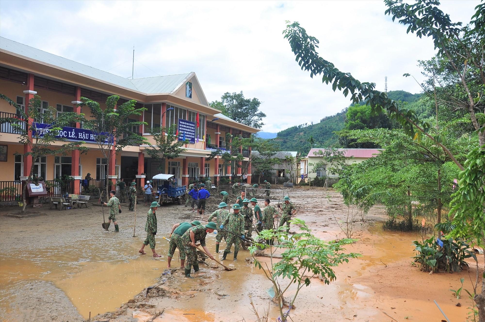 Bộ đội, thanh niên giúp Trường Phổ thông dân tộc bán trú tiểu học Trà Leng dọn dẹp bùn đất sau lũ. Ảnh: VINH ANH