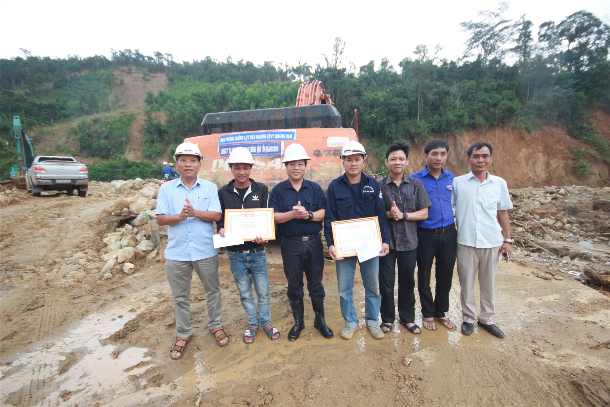 Ông Văn Anh Tuấn cùng đoàn công tác của Sở Giao thông vận tải đến động viên, tặng giấy khen cho hai lái máy công trình có nhiều nỗ lực trong việc thông tuyến vào xã Phước Thành, Phước Lộc. Ảnh: T.C
