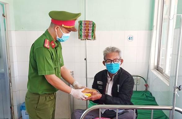 Đại diện Đoàn Thanh niên Công an tỉnh phát khẩu trang cho bệnh nhân. Ảnh: NN
