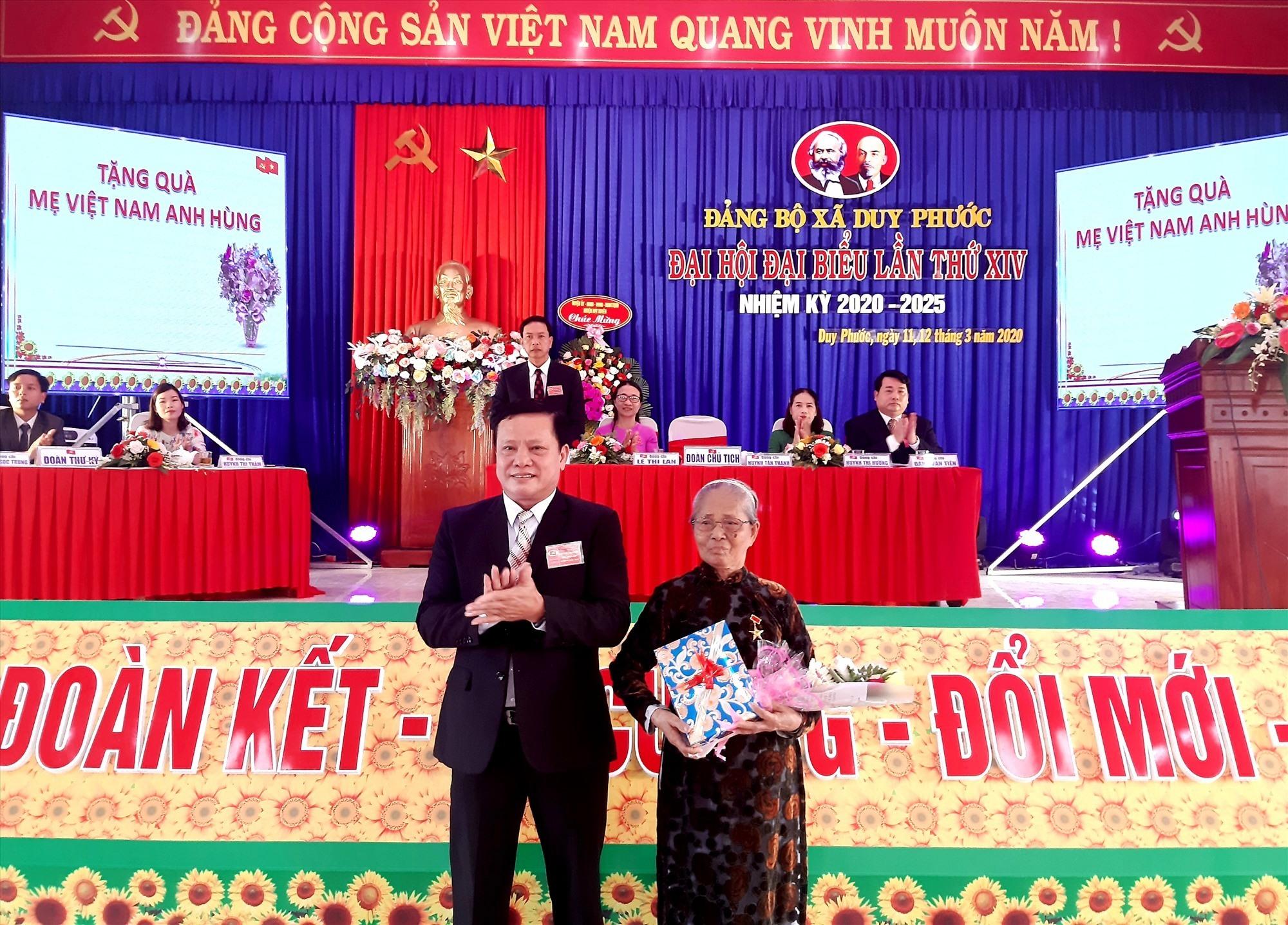 Ông Huỳnh Tấn Thành - Bí thư Đảng ủy xã Duy Phước (khóa XIII) tặng quà Bà mẹ VNAH Dương Thị Phụng trong phiên khai mạc Đại hội. Ảnh: V.S