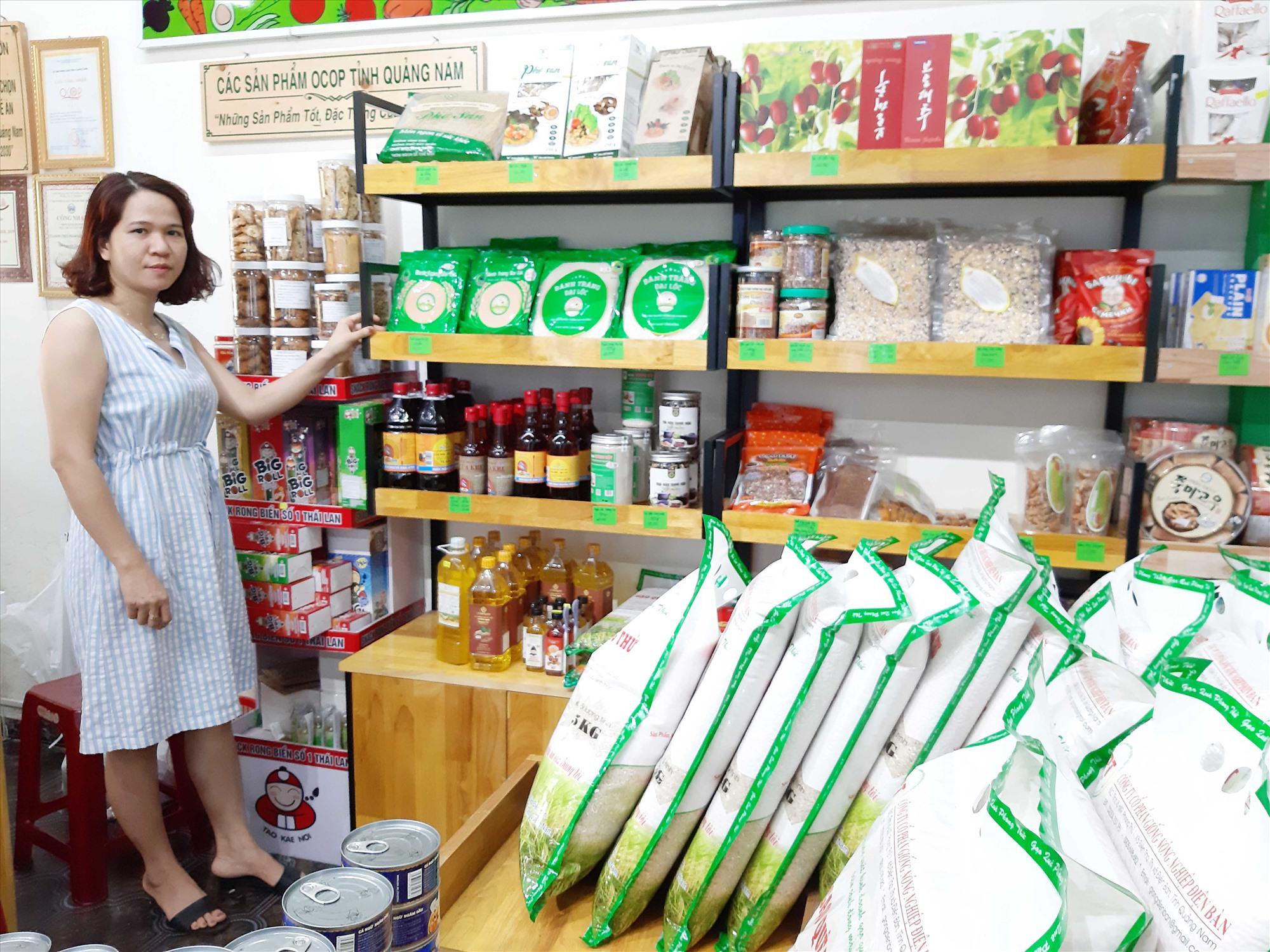 Chị Hồ Thị Bông, chủ cơ sở kinh doanh Quê Vườn bên kệ hàng OCOP. Ảnh: L.H