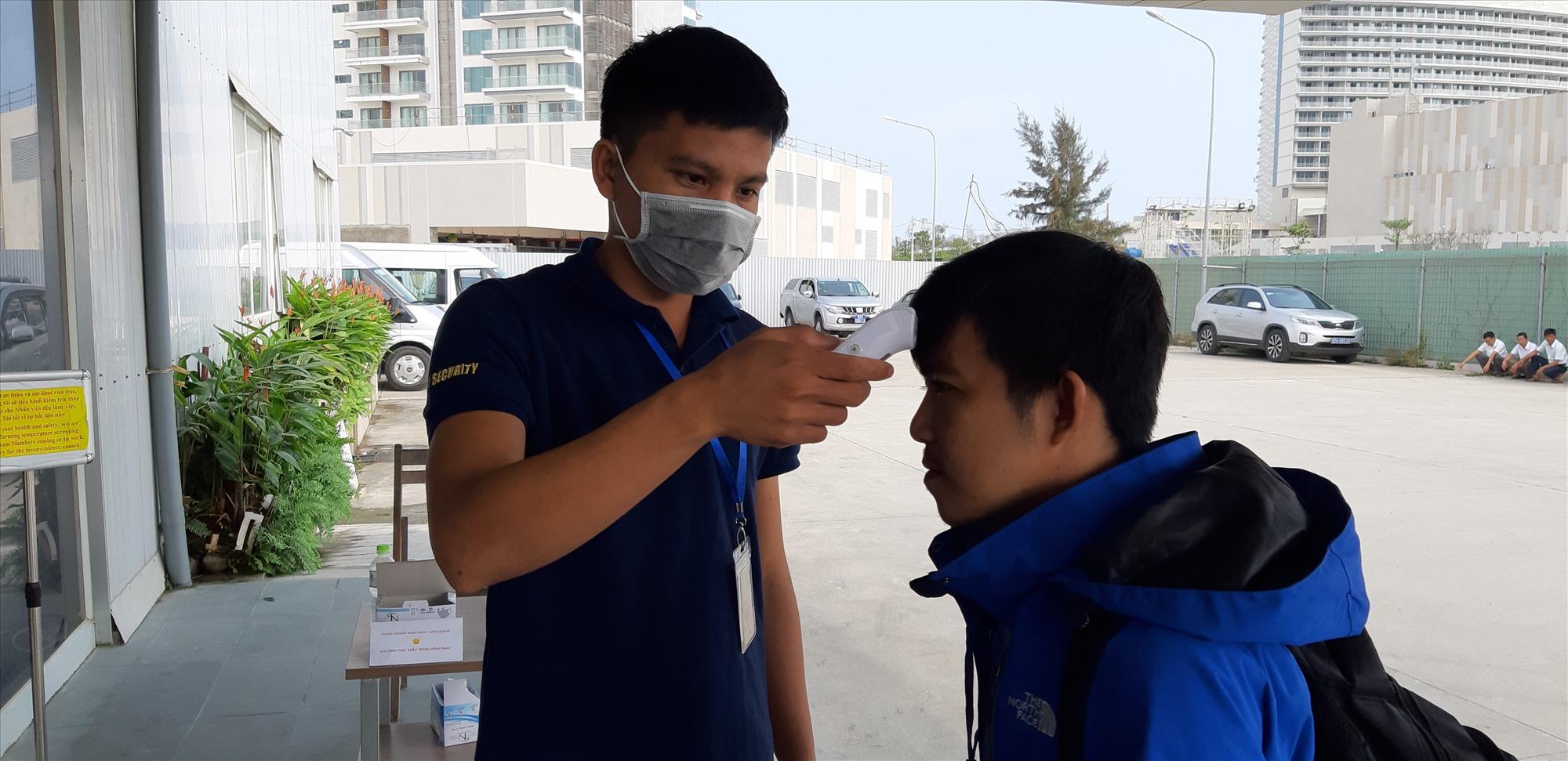 Công ty TNHH Phát triển Nam Hội An tổ chức đo thân nhiệt thường xuyên đối với tất cả những người vào khu vực công trường.      Ảnh: HOÀI NHI