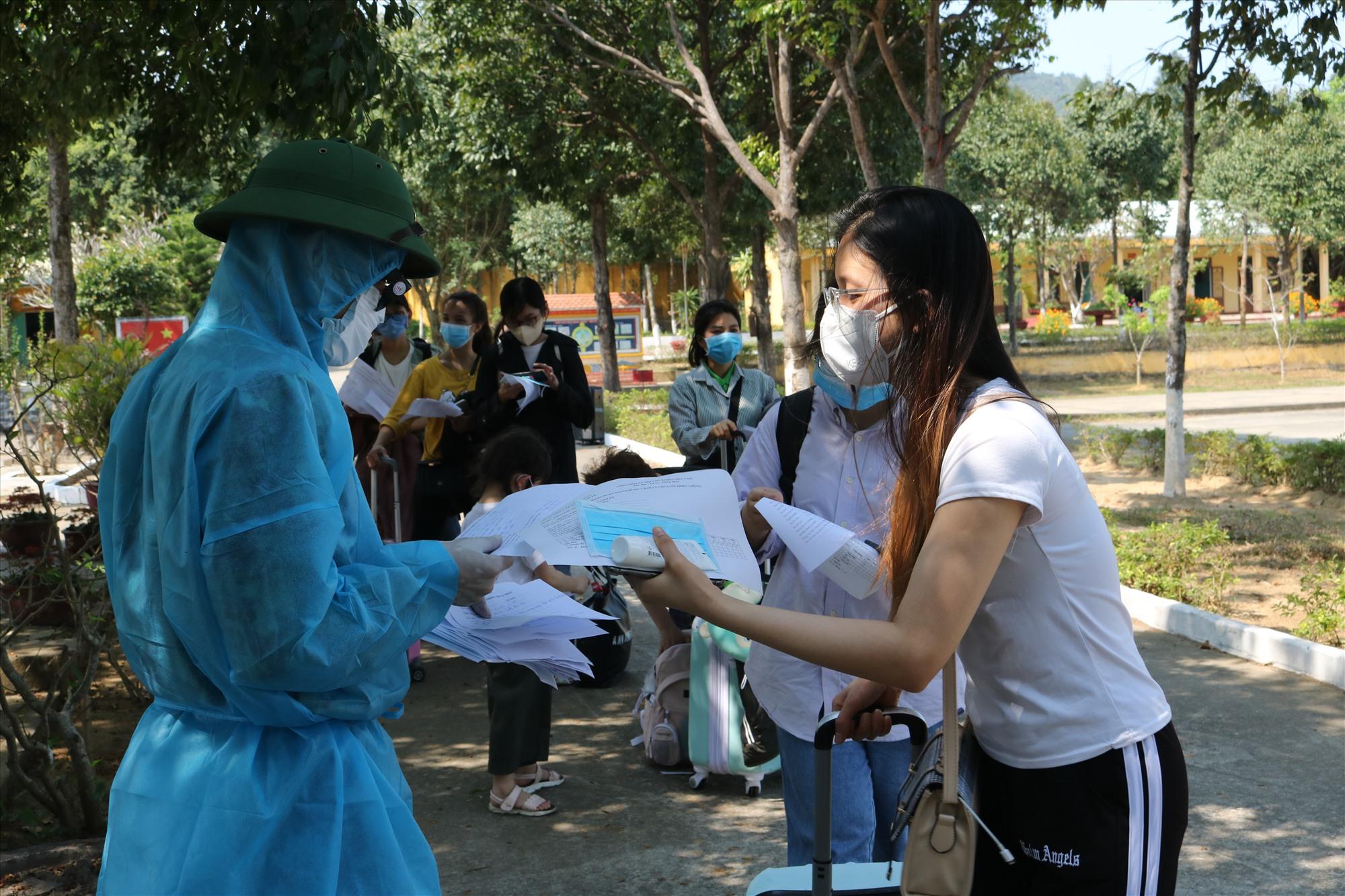 Bộ đội hướng dẫn công dân viết tờ khai y tế trước khi vào khu cách ly. Ảnh: V.H