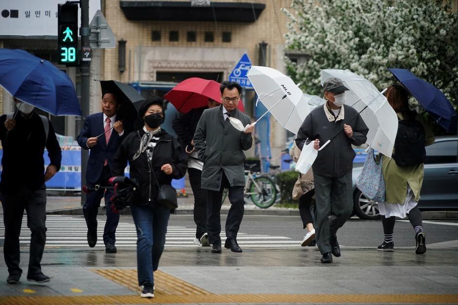 Nhiều người Hàn Quốc trở lại văn phòng làm việc sau khi các biện pháp giãn cách xã hội được nới lỏng. Ảnh: Reuters