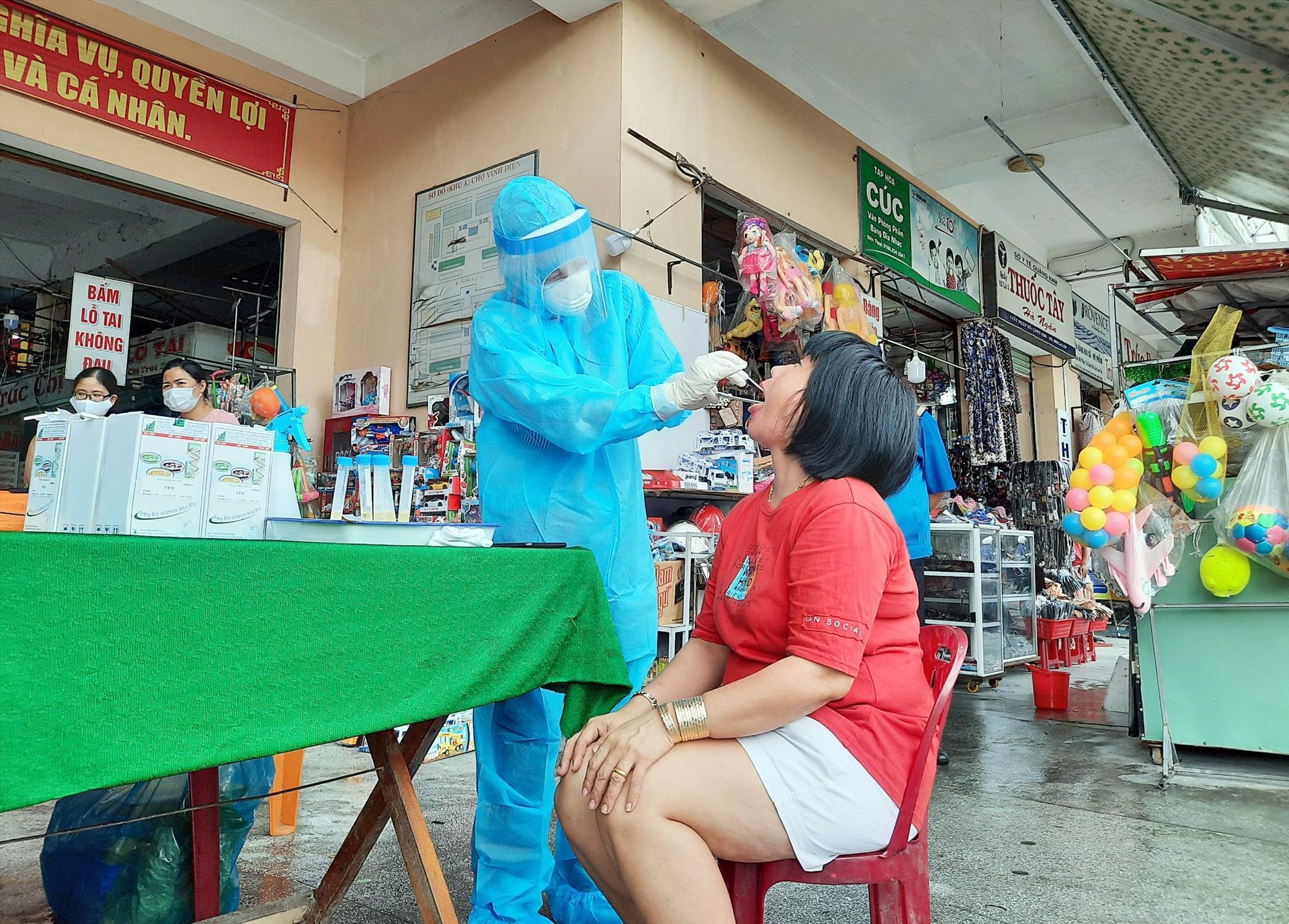 CDC Quảng Nam thực hiện lấy mẫu xét nghiệm ở chợ Vĩnh Điện. Ảnh: D.L