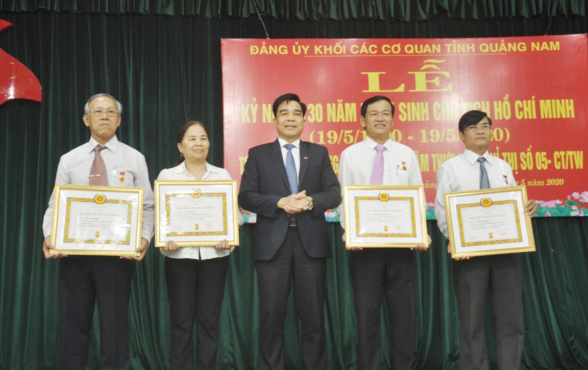 Thay mặt Ban Thường vụ Tỉnh ủy, Phó Bí thư Thường trực Tỉnh ủy Lê Văn Dũng trao tặng Huy hiệu Đảng cho các đảng viên. Ảnh: N.Đ