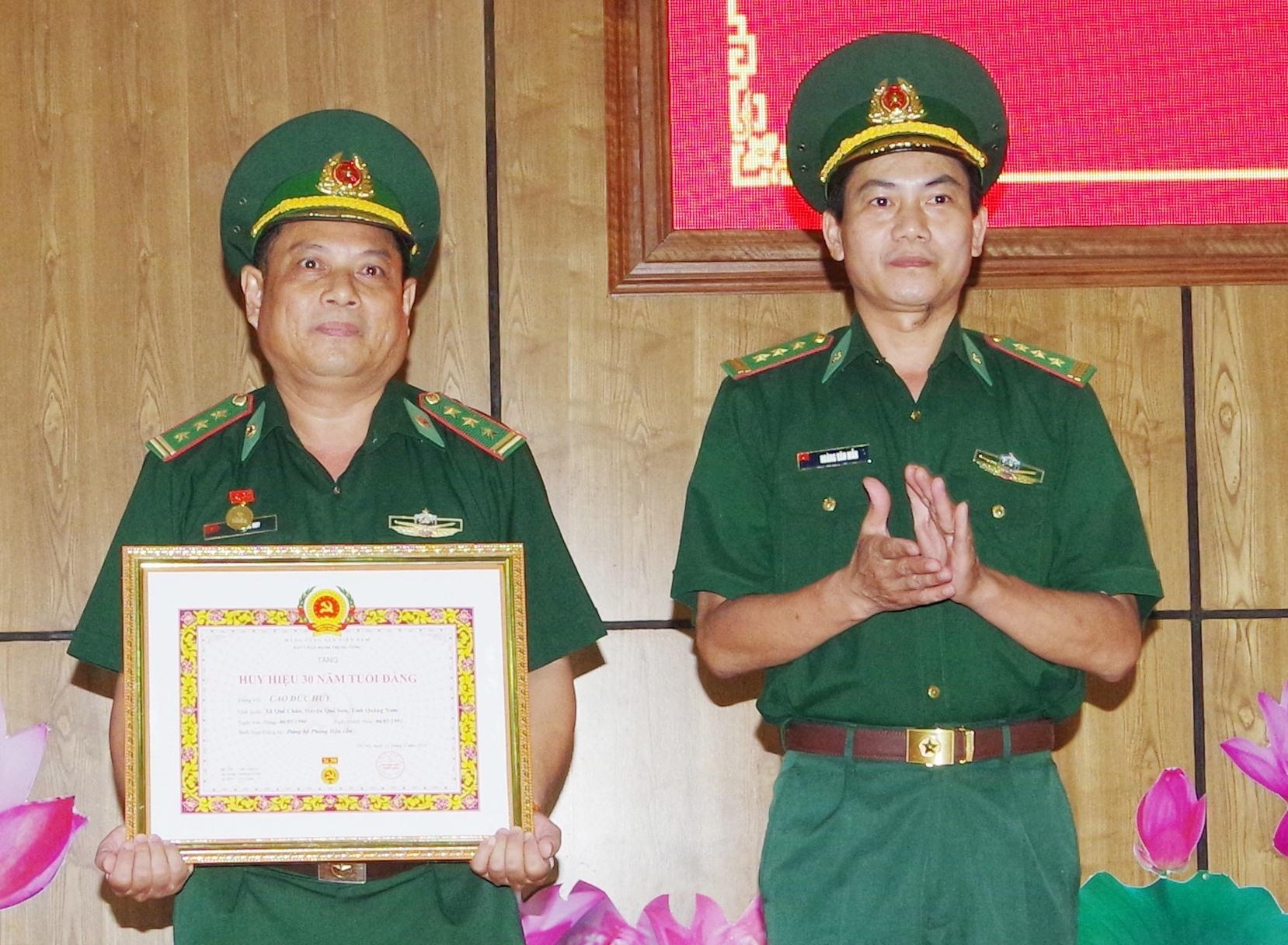 Thượng tá Hoàng văn Mẫn, Bí thư Đảng ủy, Chính ủy BĐBP tỉnh trao huy 30 năm tuổi Đảng cho đồng chí Cao Đức Huy. Ảnh: HUỲNH CHÍN