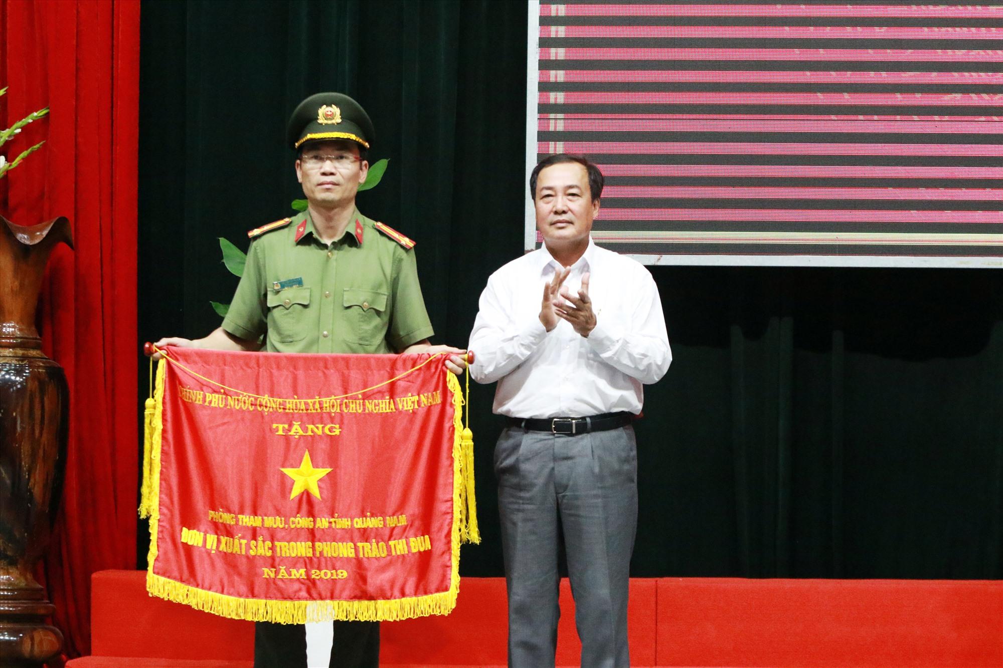Phó Chủ tịch Thường trực UBND tỉnh Huỳnh Khánh Toàn thừa ủy nhiệm trao Cờ đơn vị xuất sắc trong phong trào thi đua năm 2019 của Chính phủ cho đại diện Phòng Tham mưu Công an tỉnh. Ảnh: T.C