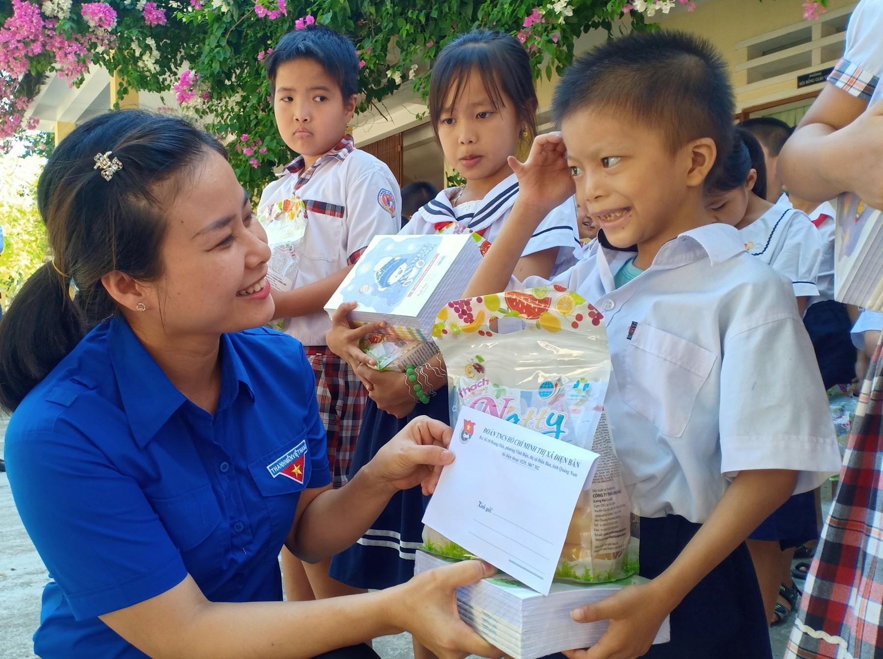 Chị Đặng Thị Bảo Trinh - Bí thư Thị đoàn, Chủ tịch Hội đồng Đội thị xã Điện Bàn tặng quà cho thiếu nhi. Ảnh: T.N