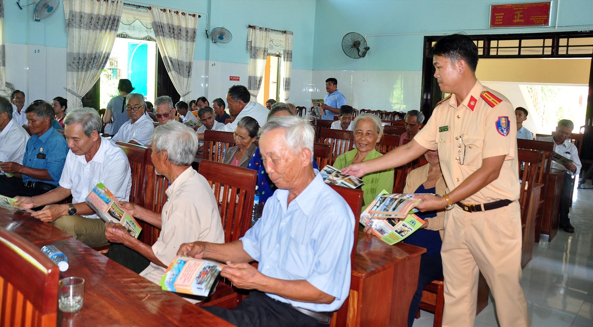 Thiếu tá Nguyễn Đình Thắng, báo cáo viên Phòng Cảnh sát đường thủy phát tờ rơi tuyên truyền pháp luật an toàn giao thông đường thủy đến cựu chiến binh xã Đại Cường. Ảnh: VINH ANH