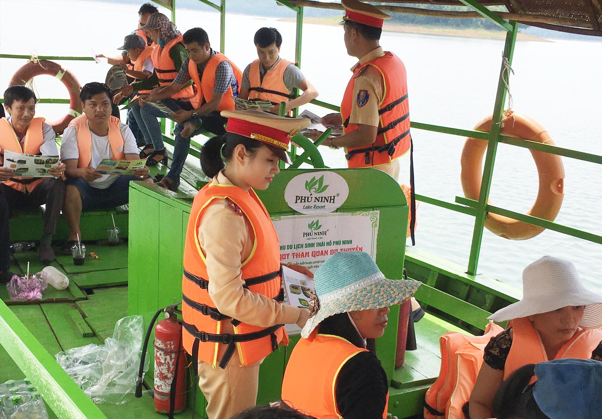 Cảnh sát đường thủy tuyên truyền, phát tờ rơi cho du khách ở hồ Phú Ninh. Ảnh: T.C