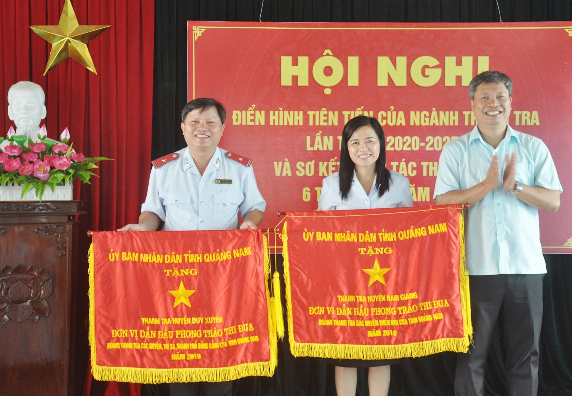 Phó Chủ tịch UBND tỉnh Hồ Quang Bửu tặng Cờ thi đua xuất sắc của UBND tỉnh cho Thanh tra huyện Duy Xuyên và Nam Giang - hai đơn vị dẫn đầu phong trào thi đua khối các địa phương miền núi và đồng bằng năm 2019. Ảnh: N.Đ