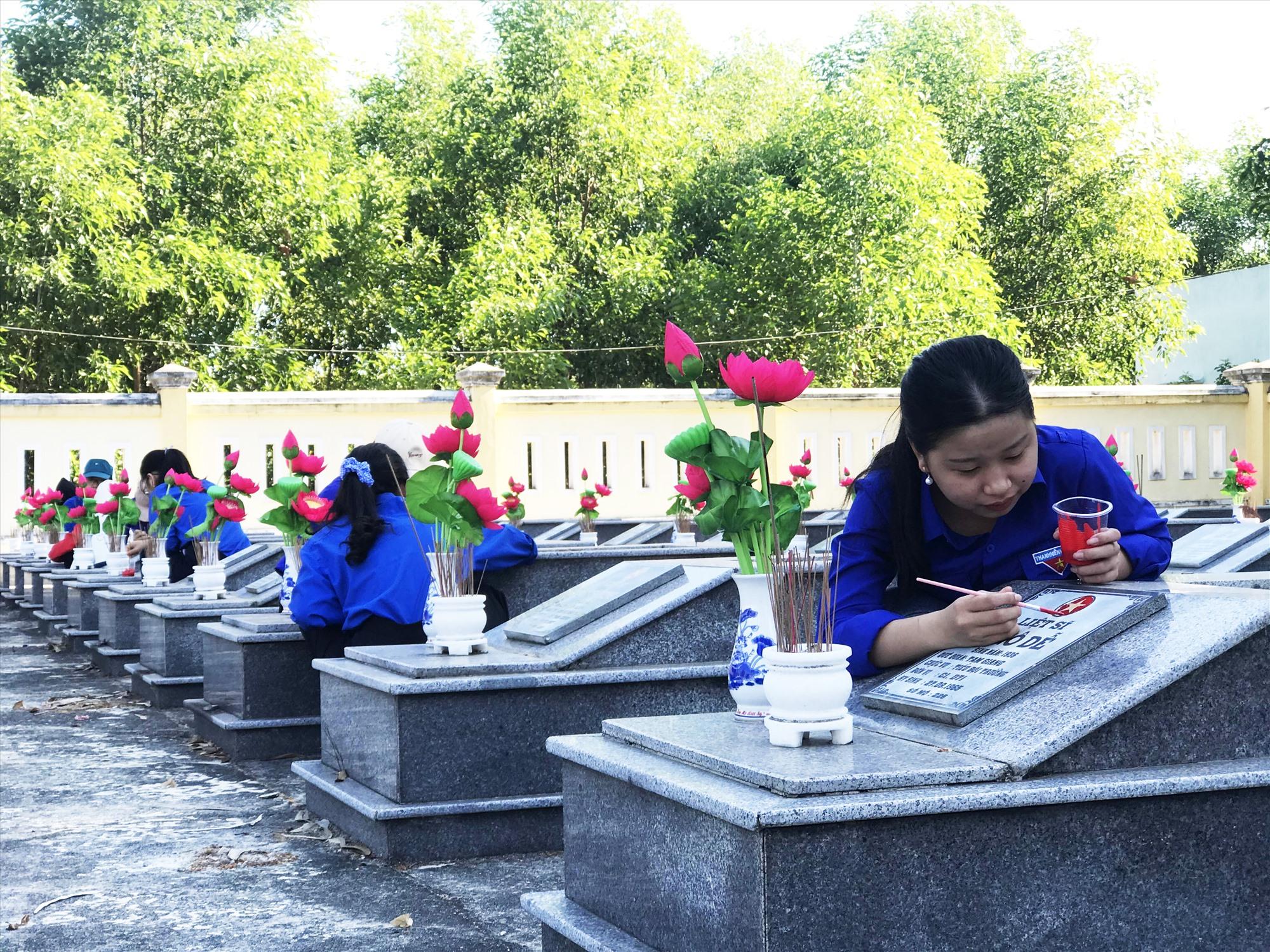 Sơn lại biểu tượng cờ Tổ quốc trên phần mộ tại Nghĩa trang liệt sĩ xã Tam Giang (Núi Thành). Ảnh: THÁI CƯỜNG