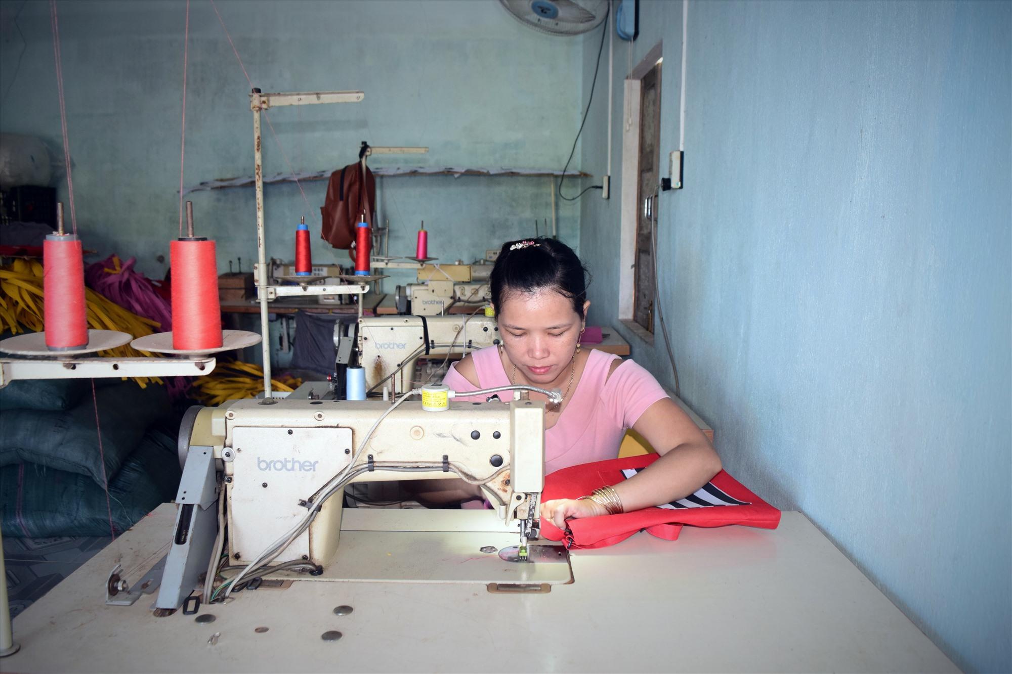 Chị Nguyễn Thị Tâm may các sản phẩm túi xách tại xưởng của mình. Ảnh: L.C