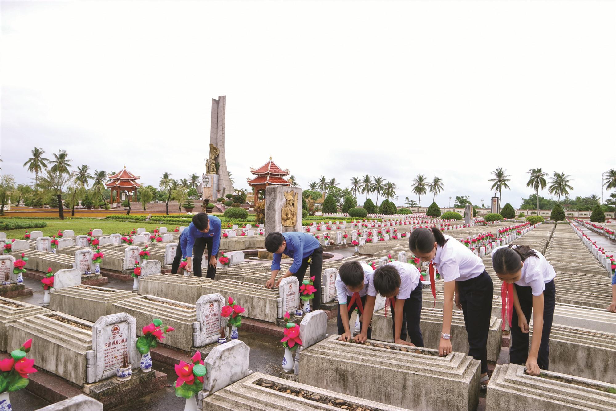 Học sinh tham gia chăm sóc phần mộ liệt sĩ ở Nghĩa trang liệt sĩ Điện Bàn. Ảnh: PHƯƠNG THẢO