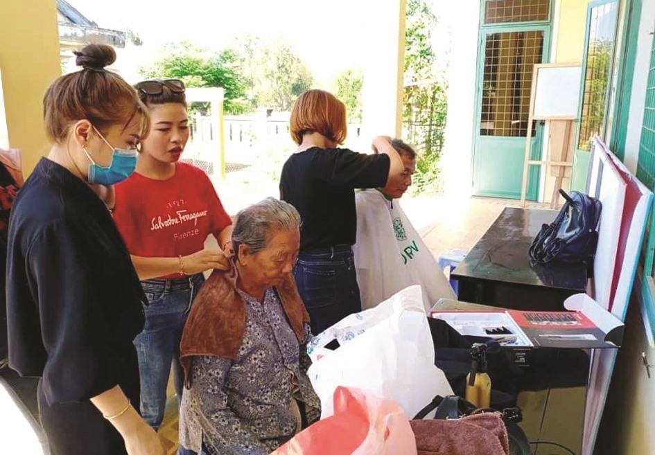 Đoàn viên thanh niên huyện Núi Thành cắt tóc cho thân nhân gia đình chính sách. Ảnh: THÁI CƯỜNG
