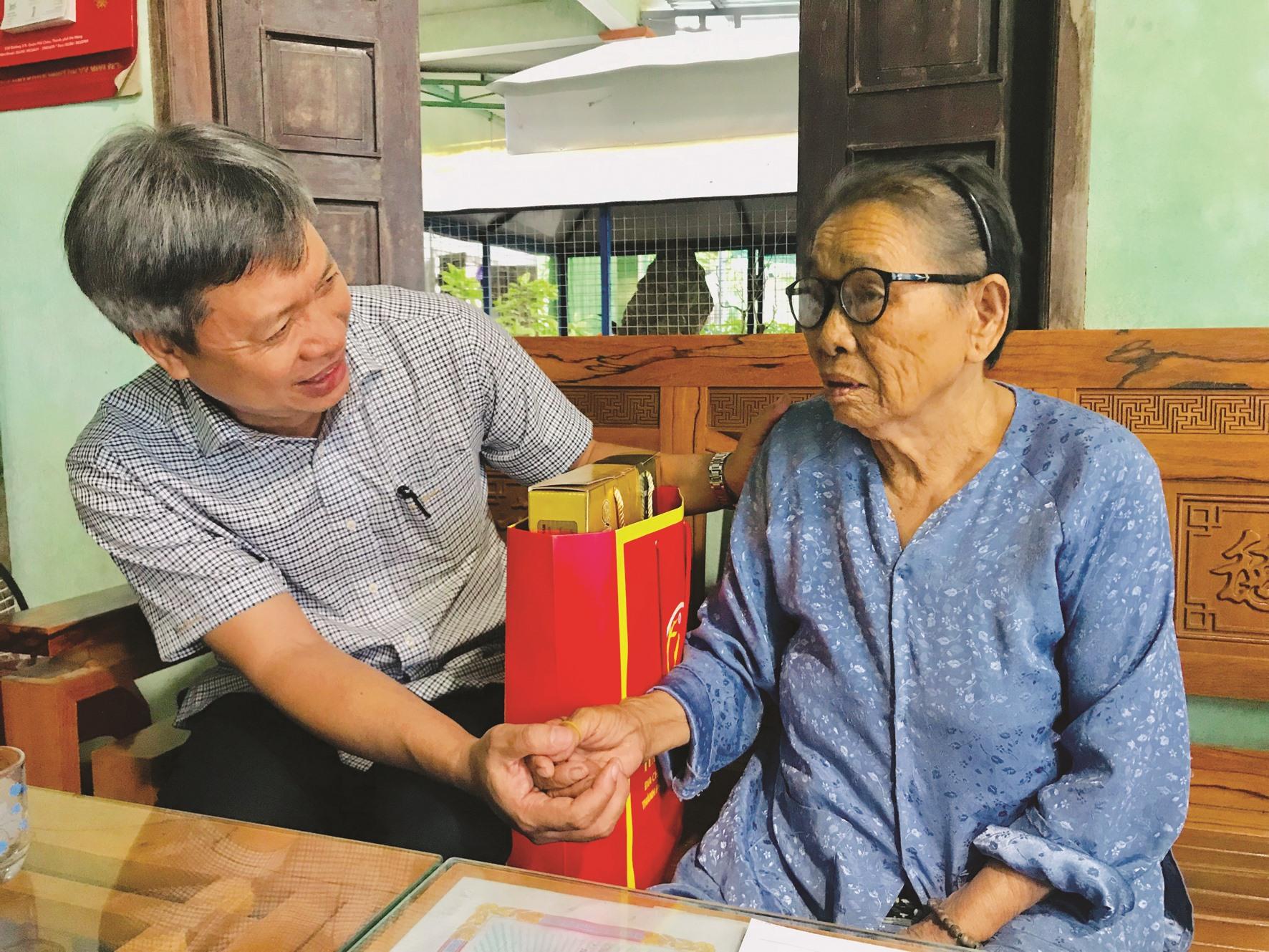 Phó Chủ tịch UBND tỉnh Hồ Quang Bửu trao quà và gửi lời chúc sức khỏe đến cụ Huỳnh Thị Thu, 83 tuổi (trú Cẩm Kim, TP. Hội An). Ảnh: QUỐC TUẤN