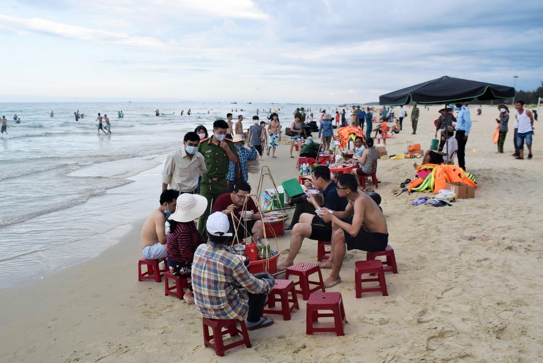 Lực lượng Công an xã Tam Thanh kịp thời nhắc nhở một số điểm chưa giữ đúng khoảng cách 1m tại bãi biển. Ảnh: HOÀI AN