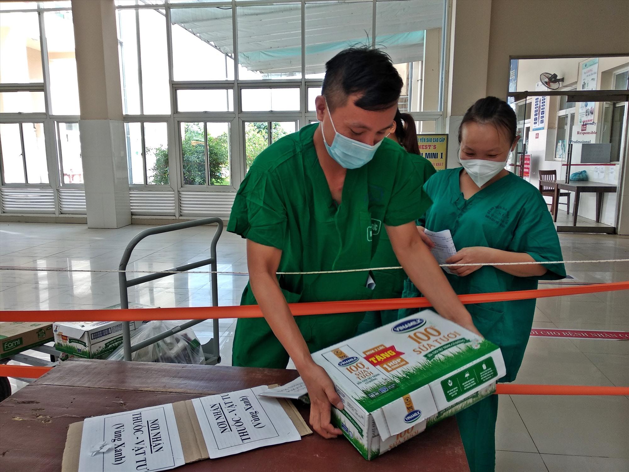 Chuyển vật tư, vật dụng cần thiết vào bên trong khu cách ly điều trị bệnh nhân SARS-CoV-2. Ảnh: THẢO ĐẠO
