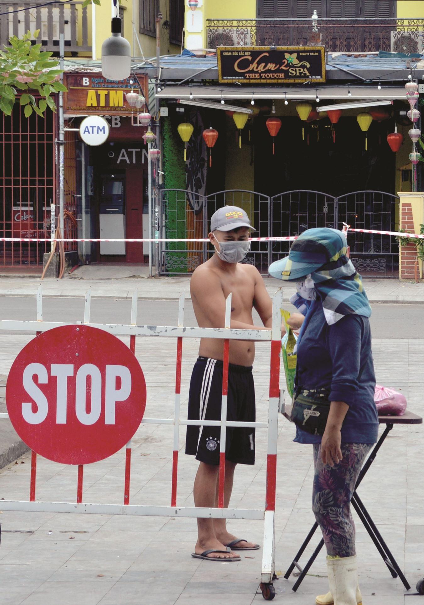 Người dân khu cách ly khối phố An Hội nhận hàng tại điểm chốt chặn.