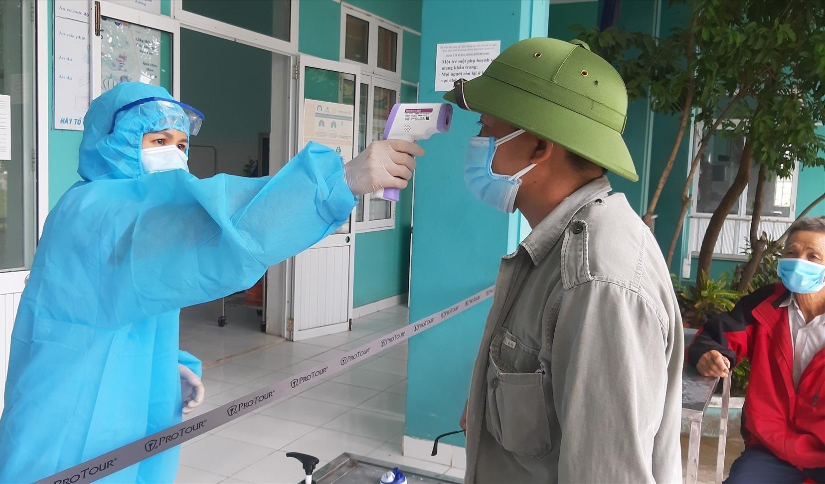 Cán bộ y tế đo thân nhiệt cho người dân xã Duy Trung nhằm sớm phát hiện những trường hợp nghi ngờ nhiễm dịch. Ảnh: T.P
