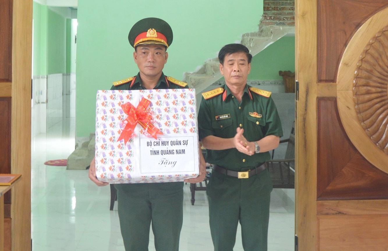 Đại tá Nguyễn Hữu Thức, Phó Chính ủy Bộ CHQS tỉnh tặng quà cho chúc mừng gia đình Đại úy Ngô Sỹ Đức.Ảnh: T.P