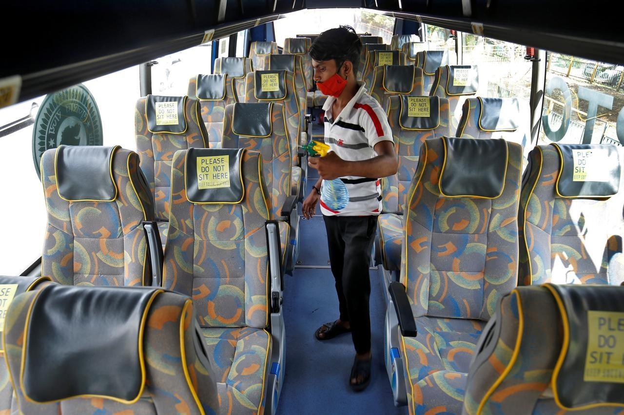 Một nhân viên khử trùng ghế ngồi của xe buýt chở khách tại Ấn Độ sau khi nhà chức trách bang Gujarat nối lại dịch vụ xe buýt sau khi nới lỏng giãn cách xã hội. Ảnh: Reuters