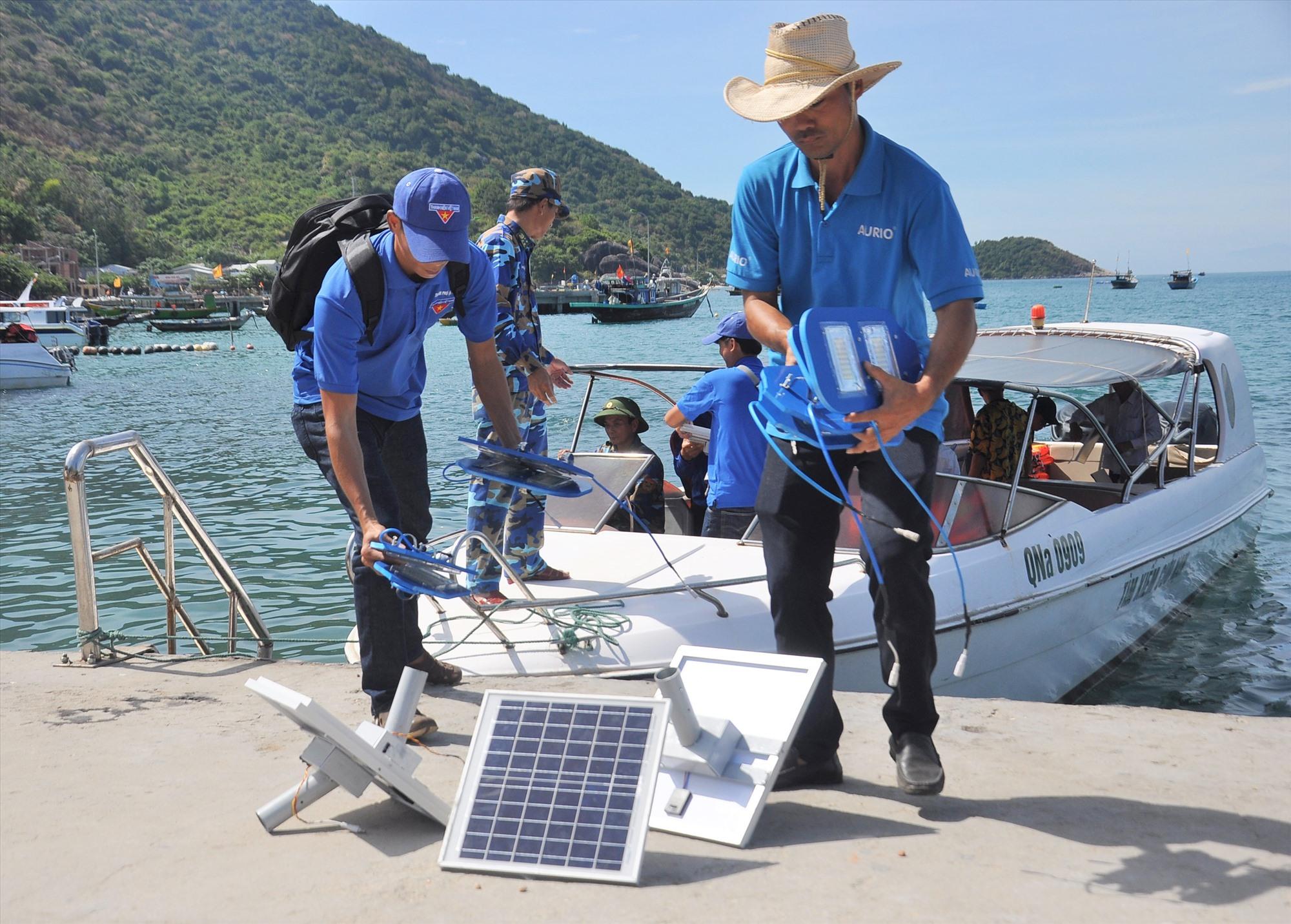Anh Phạm Phú Hiển (phải) lắp đặt đèn năng lượng mặt trời tại đảo Cù Lao Chàm (xã Tân Hiệp, TP.Hội An). Ảnh: VINH ANH