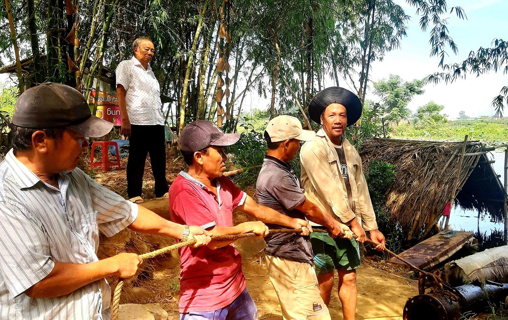 Ông Mai Năm (đứng phía sau) thuê dàn máy bơm hút nước chống hạn cho hơn 220ha lúa của người dân trong vụ hè thu 2020. Ảnh: T.P