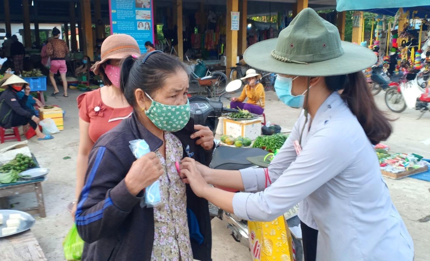 Gia đình phật Tam Hòa (Đại Quang, Đại Lộc) tặng khẩu trang và cài hoa hồng lên ngực áo người dân. Ảnh: PGQN