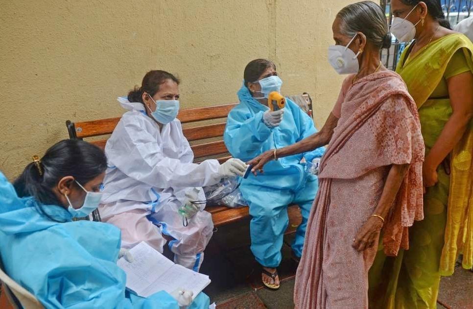 Nhân viên y tế đo nồng độ ô xy và kiểm tra nhiệt độ người dân tại Mumbai, Ấn Độ. Ảnh: AFP