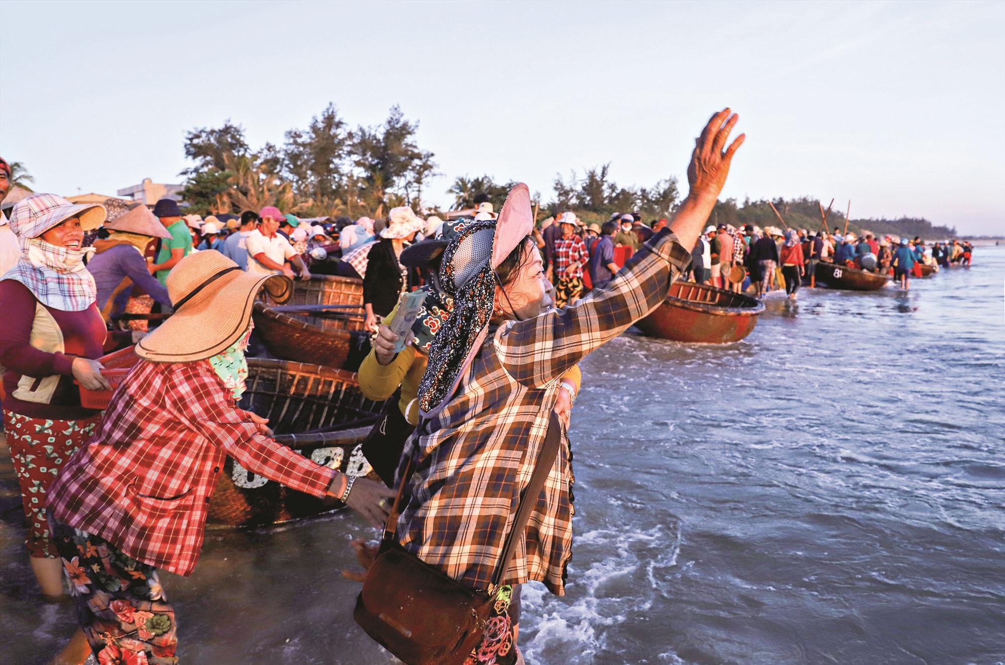 Họ lội ra mép sóng, vẫy tay từng chiếc thúng đang chở cá, mực vào bờ.