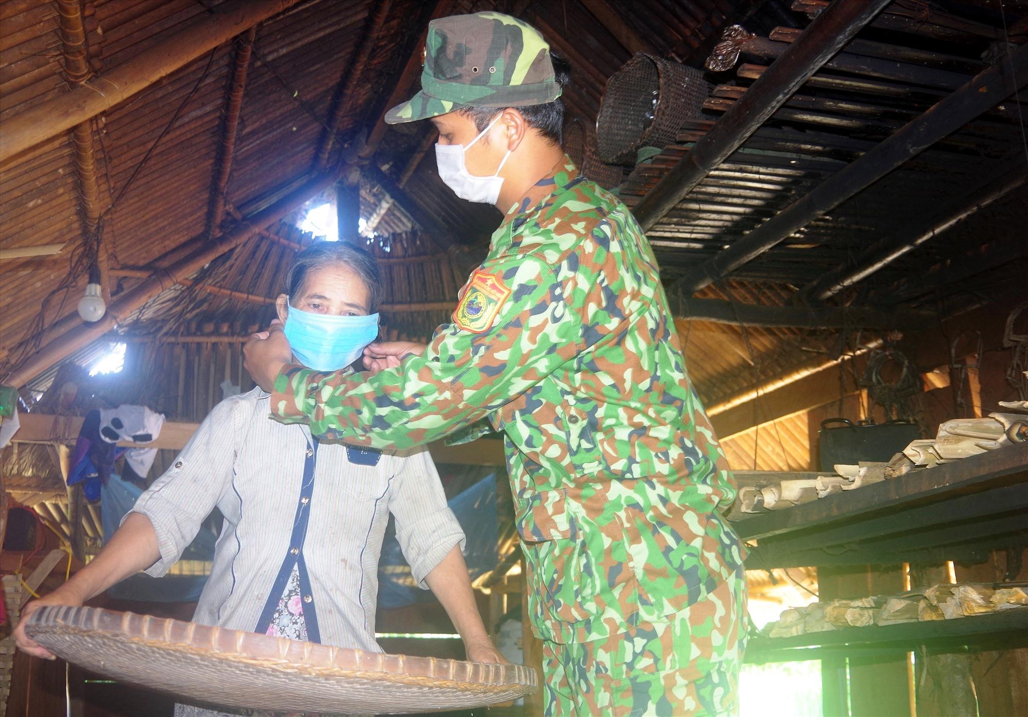 Không chỉ trực gác, cán bộ chiến sĩ còn đến từng nhà người dân để hướng dẫn việc đeo khẩu trang đúng cách. Ảnh: T.N