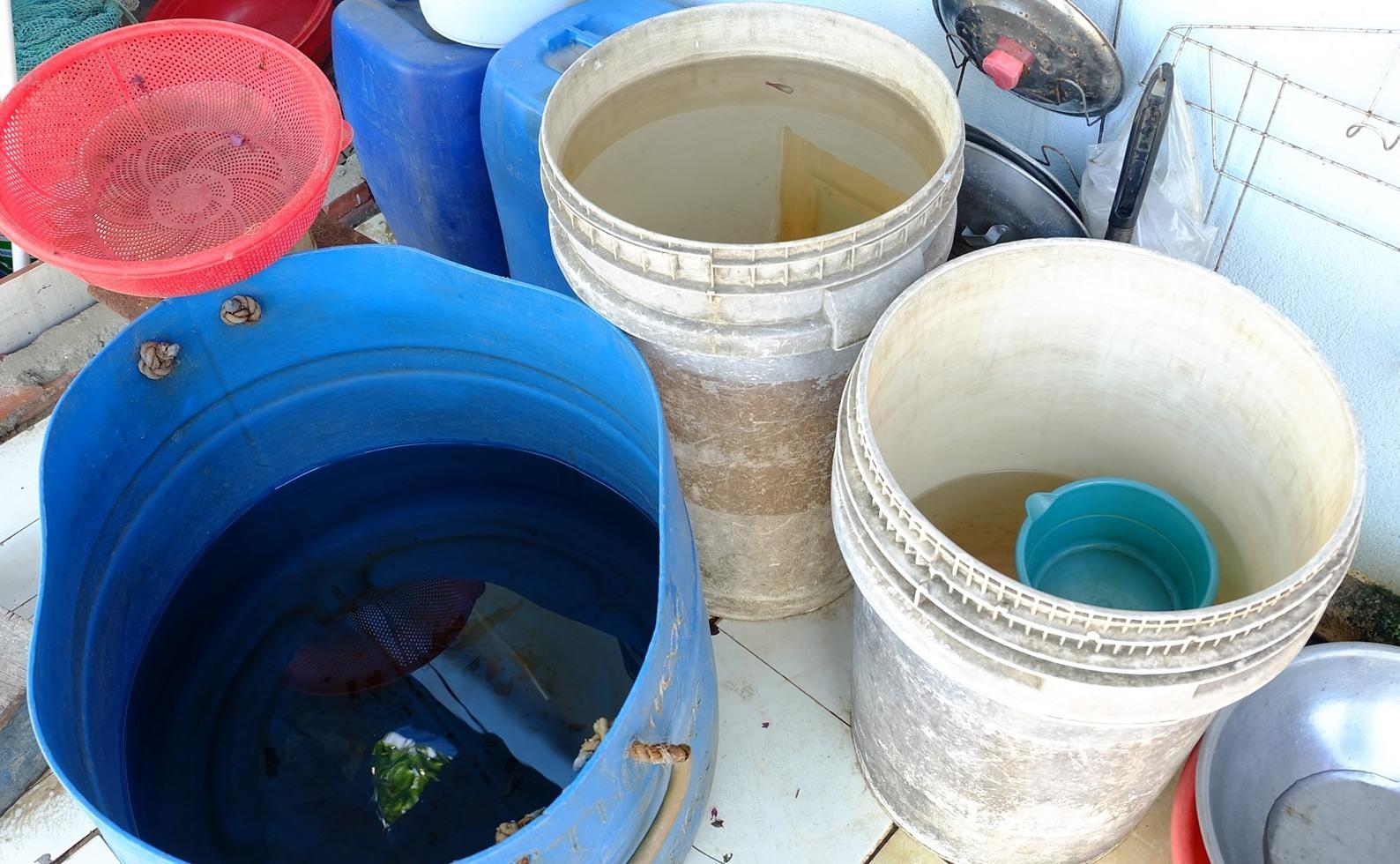 Người dân phải xin, trữ từng xô nước để sử dụng. Ảnh: A.B