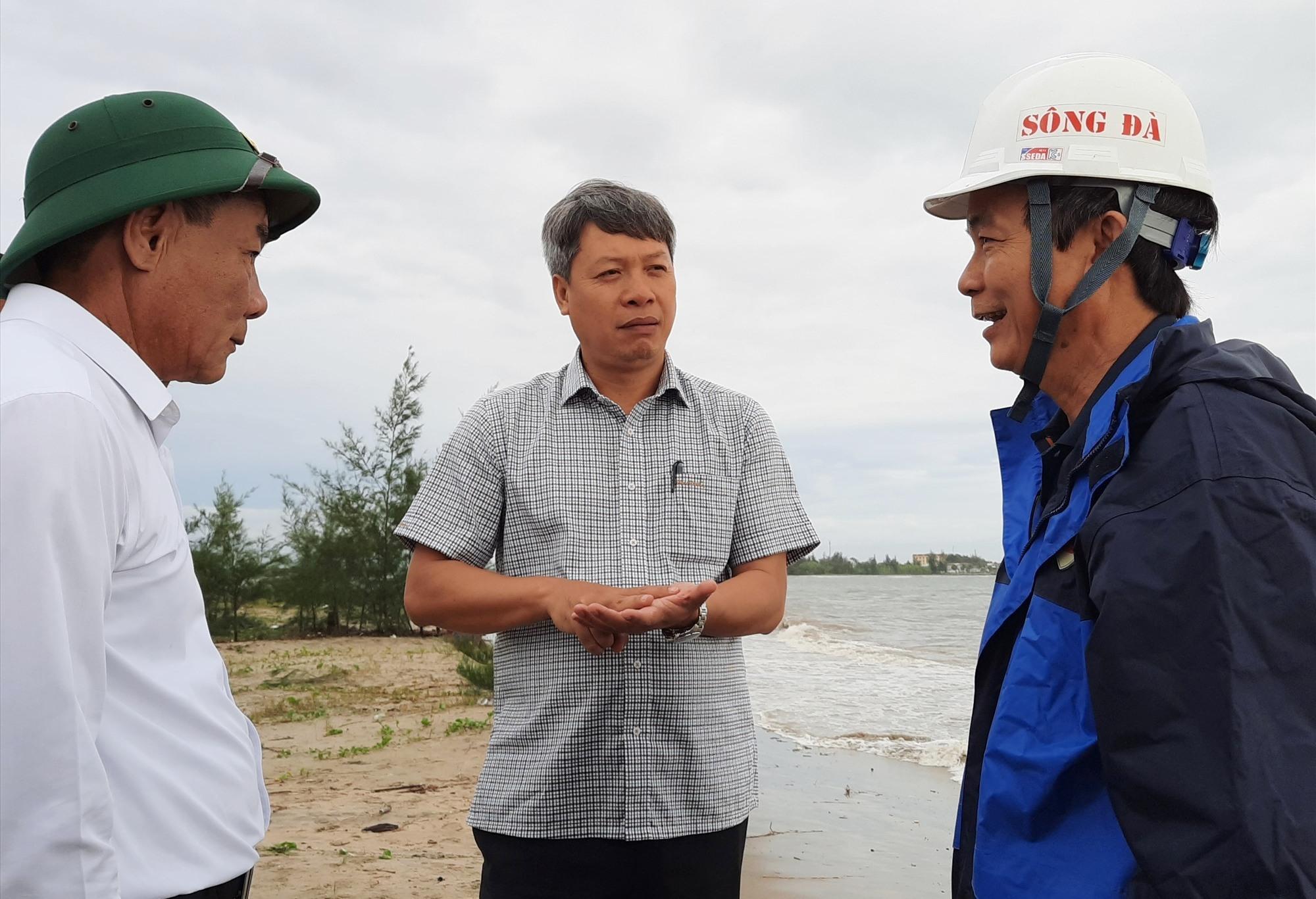 Phó Chủ tịch UBND Hồ Quang Bửu lắng nghe báo cáo của UBND huyện Duy Xuyên về tình hình sạt lở bờ biển tại xã Duy Hải. Ảnh: HỒ QUÂN