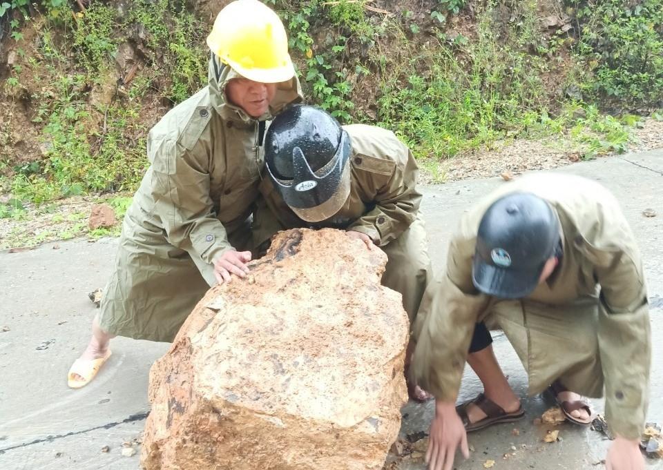 Lực lượng chức năng dọn dẹp đất, đá ở điểm sạt lở. Ảnh MINH THÔNG