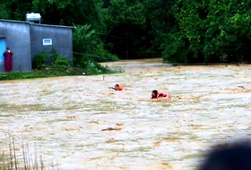 """Từng lượt người dân được đưa qua khỏi dòng nước lũ. Nhiều người chứng kiến không khỏi """"thót tim"""". Ảnh: H.B"""