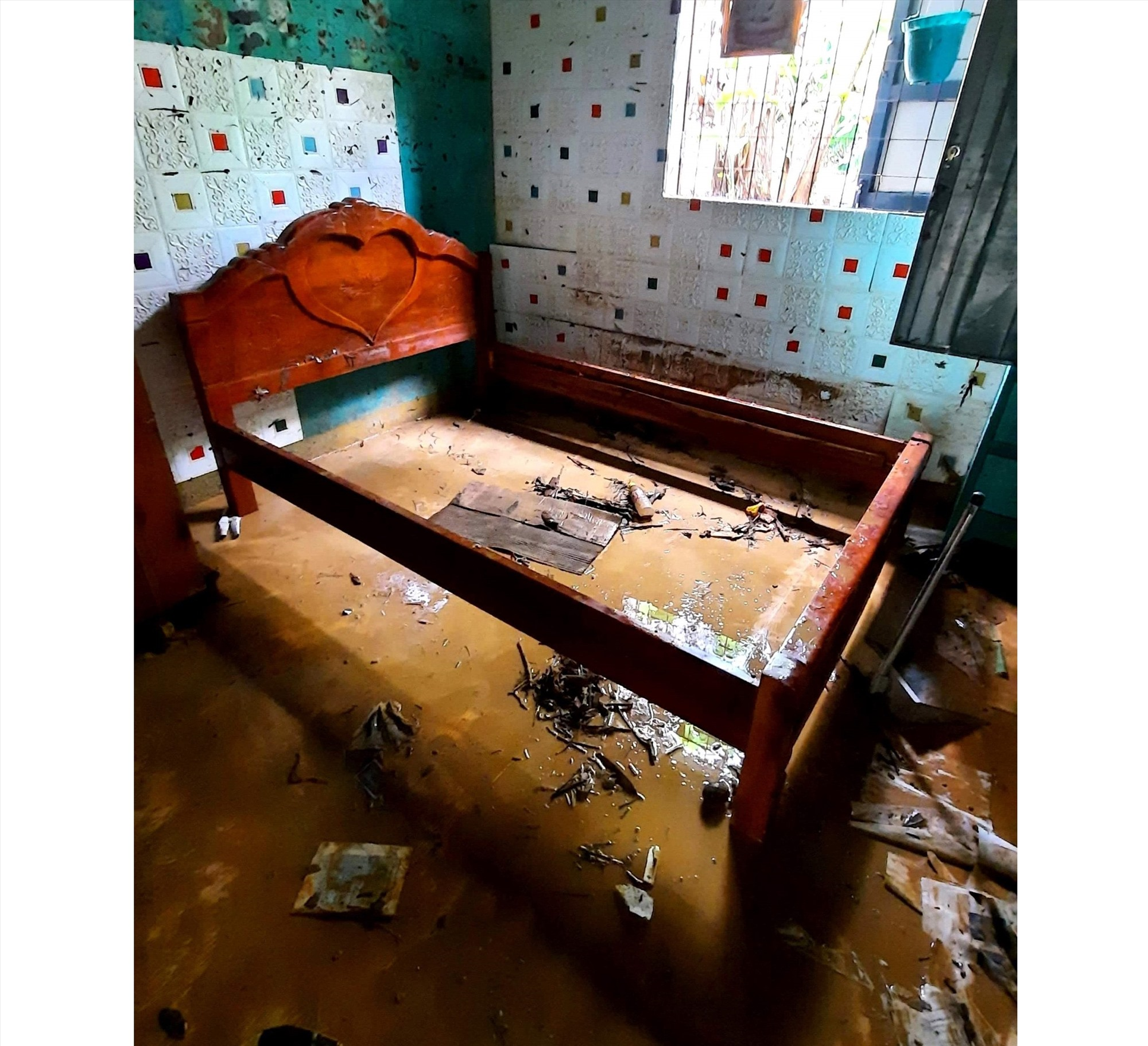 Căn phòng chỉ còn lại khung giường dính đầy bùn đất. Ảnh: N.D