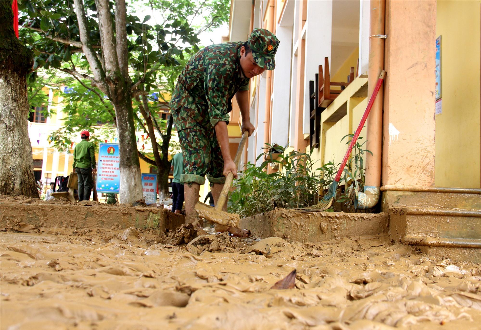 Sau lũ, lớp bùn đất đọng lại dày hơn 20cm. Các chiến sĩ phải dùng xẻng để xúc, hốt. Ảnh: A.N
