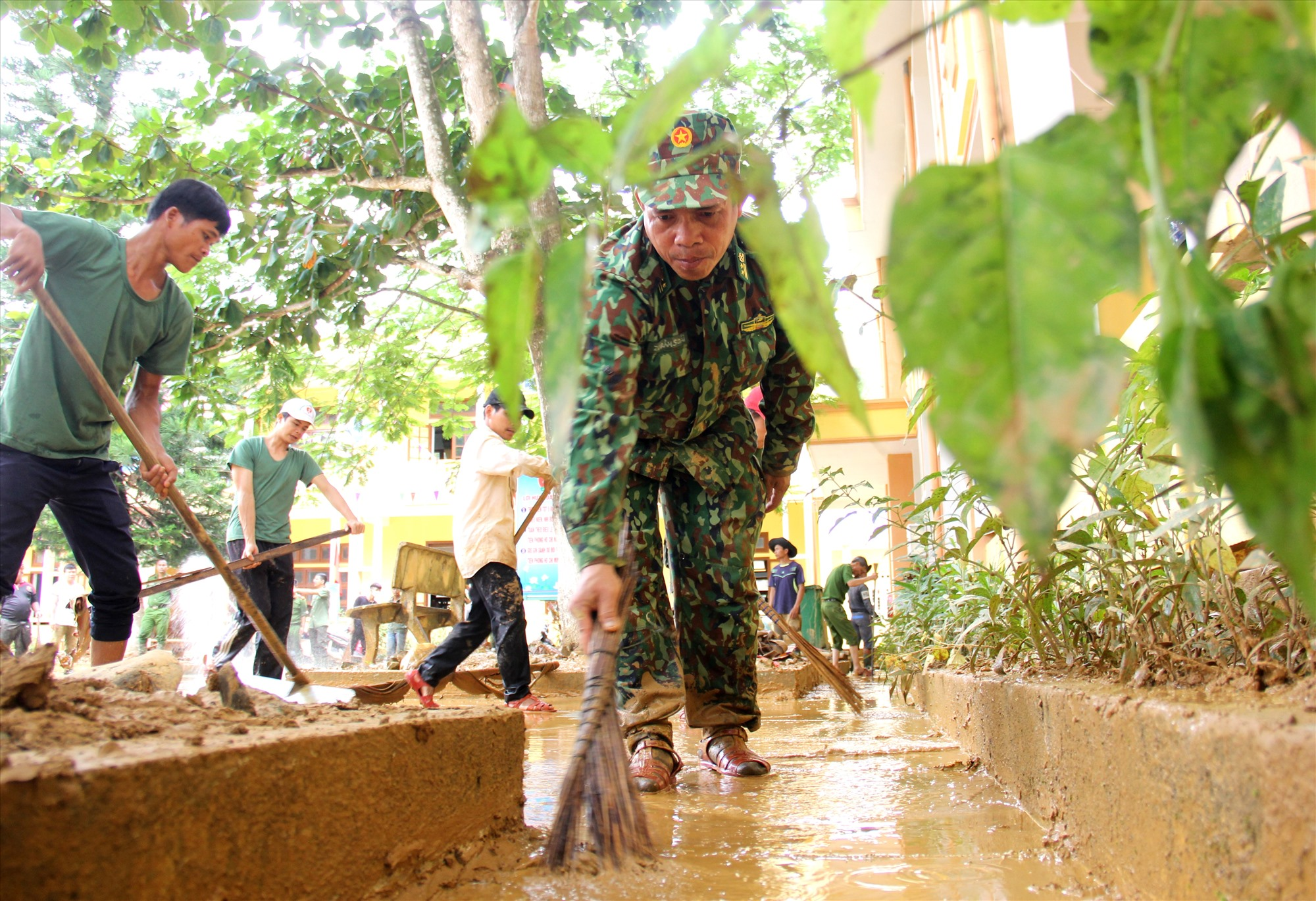 Một chiến sĩ biên phòng hăng say quét dọn sân trường. Ảnh: A.N